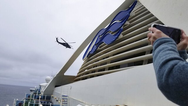 CORRECTS FROM COAST GUARD TO NATIONAL GUARD HELICOPTER- In this photo provided by Michele Smith, a National Guard  helicopter delivering virus testing kits hovers above the Grand Princess cruise ship Thursday, March 5, 2020, off the California coast. Scrambling to keep the coronavirus at bay, officials ordered a cruise ship with about 3,500 people aboard to hold off the California coast Thursday until passengers and crew could be tested, after a traveler from its previous voyage died and at least one other became infected. Princess Cruises says fewer than 100 of those aboard have been identified for testing. (Michele Smith via AP)