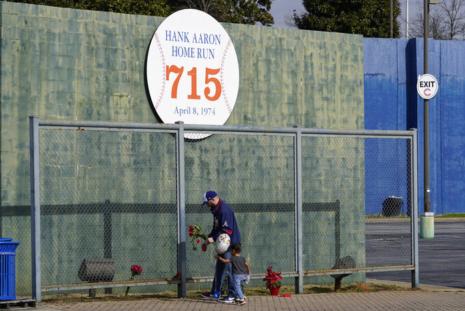 Les Motes and his two-year-old daughter Mahalia leave flowers, Friday, Jan. 22, 2021, in Atlanta, near the spot where a ball hit for a home run by Atlanta Braves' Hank Aaron cleared the wall to break Babe Ruth's career home run record in 1974. Aaron, who endured racist threats with stoic dignity during his pursuit of Babe Ruth but went on to break the career home run record in the pre-steroids era, died peacefully in his sleep early Friday. He was 86. (AP Photo/John Bazemore)