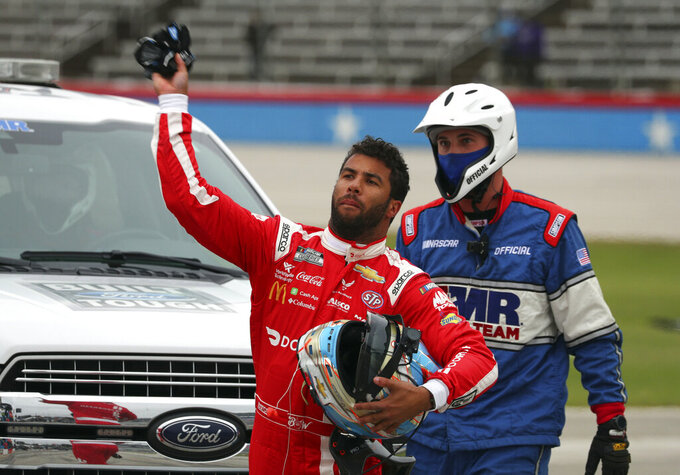 Bubba Wallace tosses his gloves while walking away from his damaged car during the NASCAR Cup Series auto race at Texas Motor Speedway in Fort Worth, Texas, Wednesday, Oct. 28, 2020. (AP Photo/Richard W. Rodriguez)