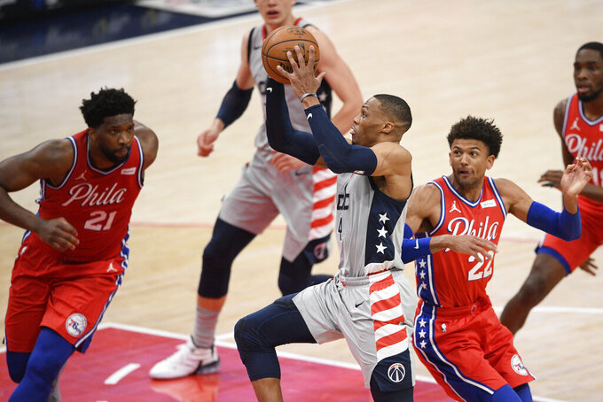 Washington Wizards guard Russell Westbrook (4) goes to the basket against Philadelphia 76ers center Joel Embiid (21) and guard Matisse Thybulle (22) during the first half of an NBA basketball game Friday, March 12, 2021, in Washington. (AP Photo/Nick Wass)