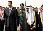 FILE - In this March 11, 2009 file photo, King Abdullah of Saudi Arabia, right, welcomes Syrian President Bashar Assad upon his arrival to attend the Arab Summit, in the Saudi capital Riyadh. Assad has survived years of war and millions of dollars in money and weapons aimed at toppling him. Now after nearly eight years of conflict, he is poised to be readmitted to the fold of Arab nations, a feat once deemed unthinkable as he brutally crushed a years-long uprising against his family's rule. (AP Photo/Hassan Ammar, File)