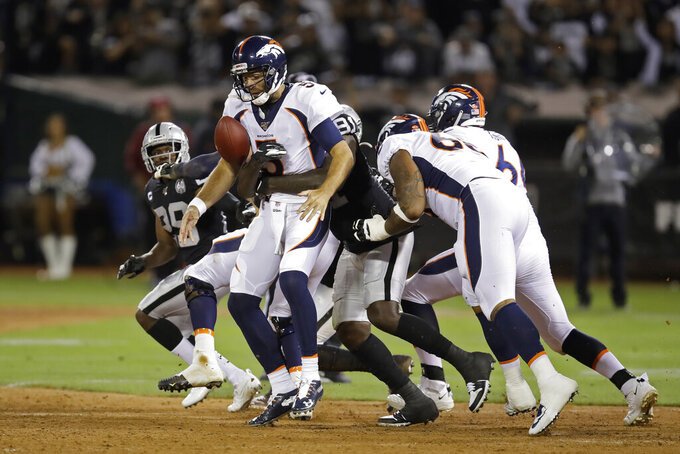 Denver Broncos quarterback Joe Flacco is sacked by Oakland Raiders defensive end Benson Mayowa during the first half of an NFL football game Monday, Sept. 9, 2019, in Oakland, Calif. (AP Photo/Ben Margot)