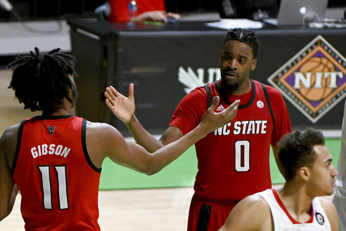 North Carolina State forward Jaylon Gibson (11) and forward DJ Funderburk (0) celebrate after a Gibson drew a foul late in the in the second half of an NCAA college basketball game against Davidson in the first round of the NIT, Thursday, March 18, 2021, in Denton, Texas. North Carolina State won 75-61. (AP Photo/Matt Strasen)