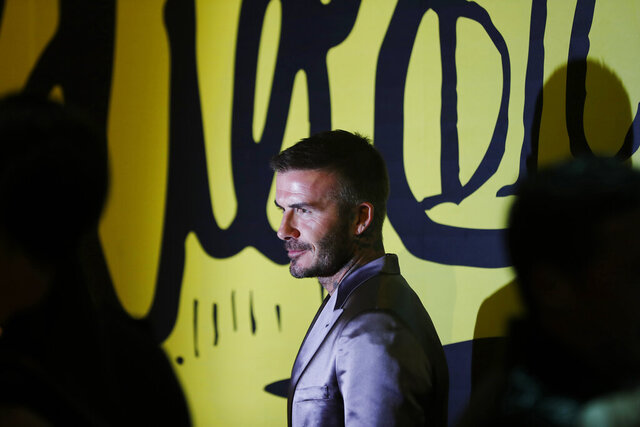 David Beckham poses for a photograph before a Christian Dior pre-fall 2020 men's fashion collection presentation during Art Basel on Tuesday, Dec. 3, 2019, in Miami. (AP Photo/Brynn Anderson)
