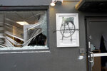 Protesters tag and smash windows at the Democratic Party of Oregon headquarters during the J20 March, Wednesday, Jan. 20, 2021, in Southeast Portland. A group of protesters carrying anti-President Joe Biden and anti-police signs marched in the streets and damaged the headquarters of the Democratic Party of Oregon.  (Beth Nakamura/The Oregonian via AP)
