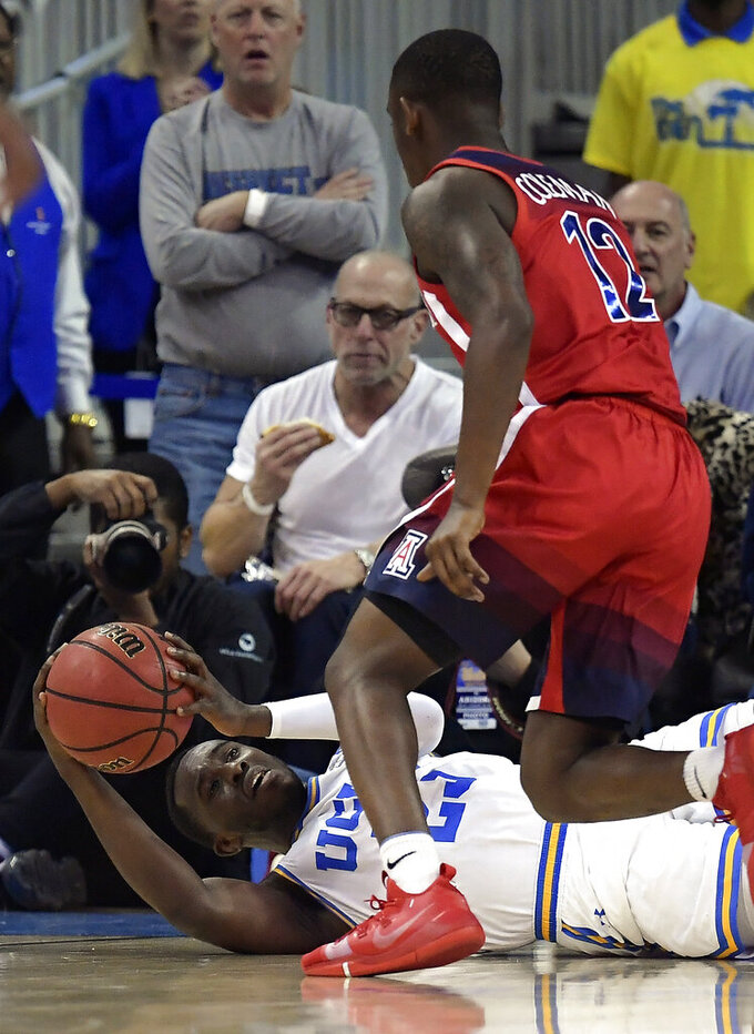 UCLA guard Prince Ali tries to pass the ball after falling while under pressure from Arizona guard Justin Coleman during the first half of an NCAA college basketball game Saturday, Jan. 26, 2019, in Los Angeles. (AP Photo/Mark J. Terrill)