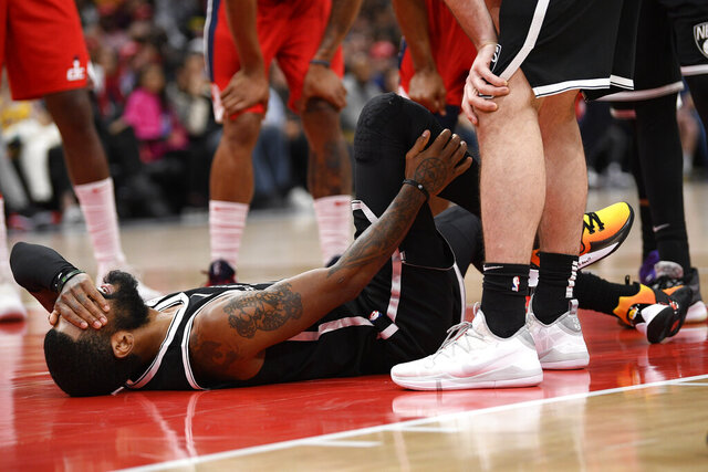 Brooklyn Nets guard Kyrie Irving reacts after he was injured during the second half of an NBA basketball game against the Washington Wizards, Saturday, Feb. 1, 2020, in Washington. (AP Photo/Nick Wass)