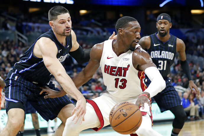 FILE - In this Feb. 1, 2020, file photo, Miami Heat forward Bam Adebayo (13) tries to get around Orlando Magic center Nikola Vucevic, left, and guard Terrence Ross (31) during the first half of an NBA basketball game in Orlando, Fla. Reporters from The Associated Press spoke to more than two dozen athletes from around the globe -- representing seven countries and 11 sports -- to get a sense of how concerned or confident they are about resuming competition. What emerged, above all, was a sense that they are going through the very same sort of calculus that much of the rest of society is: What is safe nowadays? (AP Photo/John Raoux, File)