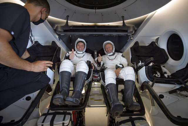NASA astronauts Robert Behnken, left, and Douglas Hurley are seen inside the SpaceX Crew Dragon Endeavour spacecraft onboard the SpaceX GO Navigator recovery ship shortly after having landed in the Gulf of Mexico off the coast of Pensacola, Fla., Sunday, Aug. 2, 2020. The Demo-2 test flight for NASA's Commercial Crew Program was the first to deliver astronauts to the International Space Station and return them safely to Earth onboard a commercially built and operated spacecraft. Behnken and Hurley returned after spending 64 days in space. (Bill Ingalls/NASA via AP)