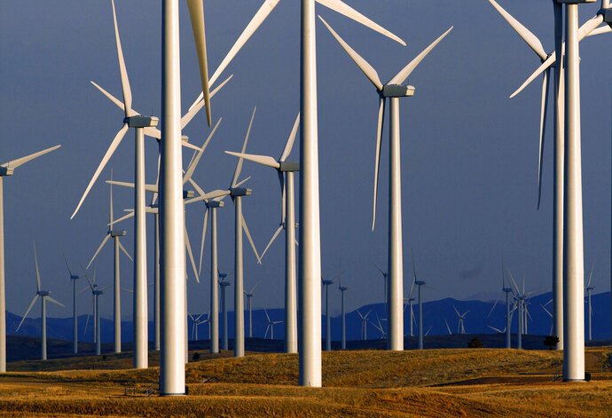 FILE - This May 6, 2013 file photo shows a wind turbine farm owned by PacifiCorp near Glenrock, Wyo. The military wants North Dakota and perhaps four other states with nuclear missile arsenals to consider new rules aimed at preventing conflicts between wind turbines and helicopters that provide security at launch facilities. Defense Department and Air Force officials were meeting Tuesday, Oct. 29, 2019 with North Dakota lawmakers and regulatory officials. (AP Photo/Matt Young, File)