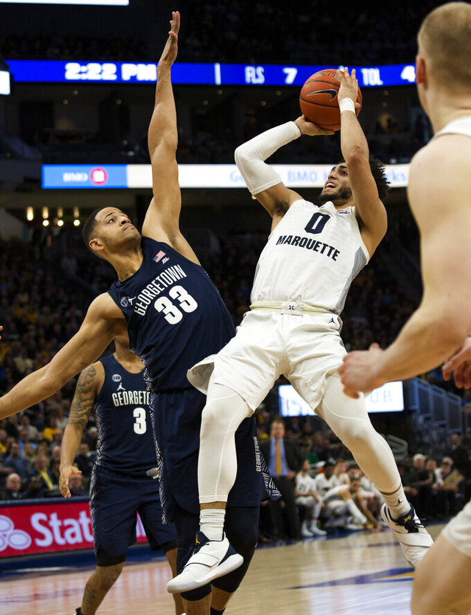 Marquette guard Markus Howard, right, goes up for a basket against Georgetown forward Trey Mourning, left, during the first half of an NCAA college basketball game Saturday, March 9, 2019, in Milwaukee. (AP Photo/Darren Hauck)