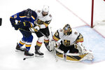 St. Louis Blues' Zach Sanford (12) and Vegas Golden Knights' Shea Theodore (27) battle in front as goalie Marc-Andre Fleury (29) makes the save during the first period of an NHL hockey playoff game Thursday, Aug. 6, 2020, in Edmonton, Alberta. (Jason Franson/Canadian Press via AP)