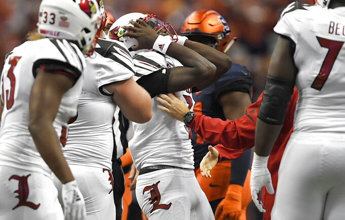 Louisville quarterback Malik Cunningham, center, holds his head as he leaves the game with an injury against Syracuse during the first half of an NCAA college football game in Syracuse, N.Y., Friday, Nov. 9, 2018. (AP Photo/Adrian Kraus)
