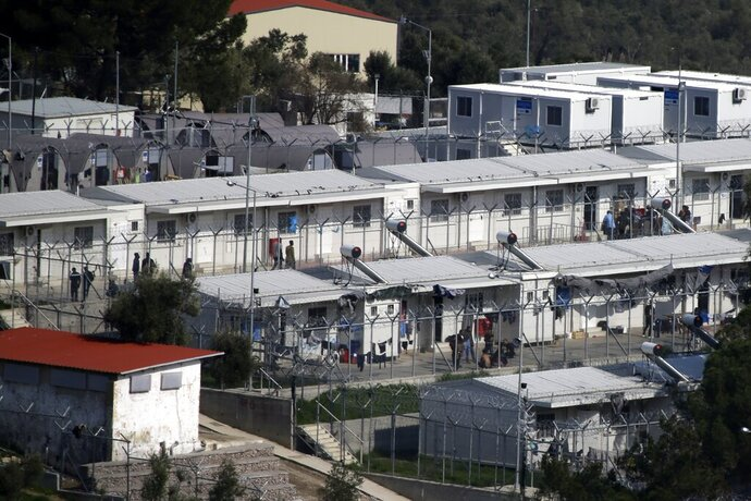 FILE - In this Wednesday, March 15, 2017 file photo, migrants walk at the Moria refugee detention center on the northeastern Greek island of Lesbos. Authorities on the Greek island of Lesbos on Friday, Sept. 20, 2019 say they are no longer able to house migrants arriving from nearby Turkey after a reception camp there had exceeded its capacity by 400%. (AP Photo/Thanassis Stavrakis, file)