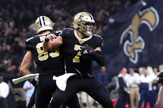 New Orleans Saints quarterback Taysom Hill (7) celebrates his touchdown reception with tight end Josh Hill in the second half of an NFL football game against the Houston Texans in New Orleans, Monday, Sept. 9, 2019. (AP Photo/Bill Feig)