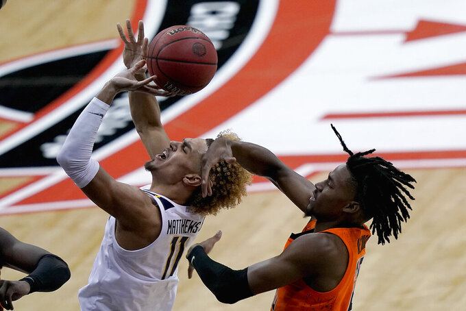 Oklahoma State's Keylan Boone, right, tries to block a shot by West Virginia's Emmitt Matthews Jr. (11) during the second half of an NCAA college basketball game in the second round of the Big 12 men's tournament in Kansas City, Mo., Thursday, March 11, 2021. Oklahoma State won 72-69. (AP Photo/Charlie Riedel)