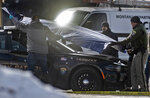 FILE - In this March 15, 2019 file photo, law enforcement officers cover Montana State Trooper Wade Palmer's patrol car at the scene of the shooting near the Evaro Bar in Missoula, Mont. The wife of trooper Palmer, who is recovering from a traumatic brain injury after being shot three times, is thanking the medical team who gave them