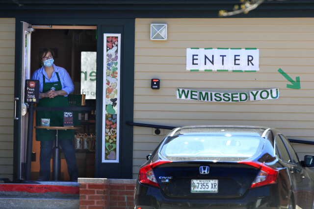 Becky Richards keeps an eye out for customers at a recently-reopened Starbucks, Wednesday, May 13, 2020, in Freeport, Maine. Business has been slow at the coffee shop as most of it's neighboring retail stores remain closed during the coronavirus pandemic. (AP Photo/Robert F. Bukaty)