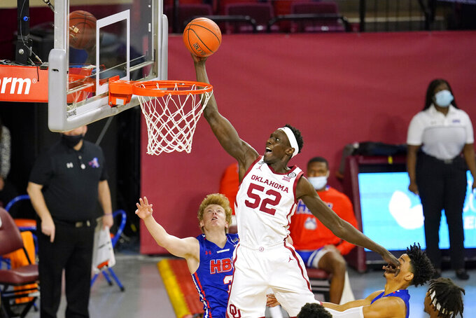 Oklahoma forward Kur Kuath (52) goes up for a dunk in front of Houston Baptist guard Brycen Long (3) and guard Pedro Castro, right, in the first half of an NCAA college basketball game Saturday, Dec. 19, 2020, in Norman, Okla. (AP Photo/Sue Ogrocki)