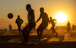 FILE - In this Aug. 19, 2020 file photo, people play soccer on a dusty field in Soweto, South Africa, The country's success in bringing its first wave of COVID-19 under control has allowed it to almost fully reopen the economy, while monitoring for signs of a second surge, says the government's chief medical advisor. (AP Photo/Themba Hadebe,File)