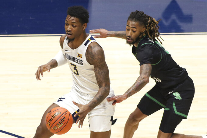 West Virginia forward Gabe Osabuohien (3) is defended by North Texas guard James Reese (0) during the first half of an NCAA college basketball game Friday, Dec. 11, 2020, in Morgantown, W.Va. (AP Photo/Kathleen Batten)