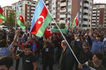 People wave Azerbaijan national flags during a funeral ceremony of a member of the Azerbaijani Armed Forces who was allegedly killed during fighting over the breakaway region of Nagorno-Karabakh in Tartar region, Azerbaijan, Wednesday, Sept. 30, 2020. Leaders of Azerbaijan and Armenia brushed off the suggestion of peace talks Tuesday, accusing each other of obstructing negotiations over the separatist territory of Nagorno-Karabakh, with dozens killed and injured in three days of heavy fighting. (AP Photo/Aziz Karimov)