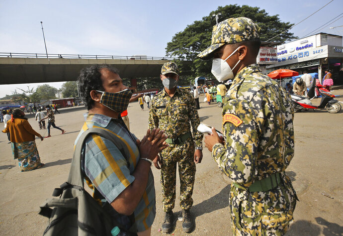 A man pleads with municipal officers as he is fined for not wearing a face mask in Bengaluru, India, Thursday, Oct. 29, 2020. India's confirmed coronavirus caseload surpassed 8 million on Thursday with daily infections dipping to the lowest level this week, as concerns grew over a major Hindu festival season and winter setting in. (AP Photo/Aijaz Rahi)