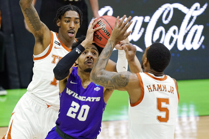 Abilene Christian's Coryon Mason (20) drives between Texas' Donovan Williams, left, and Royce Hamm Jr. (5) during the first half of a college basketball game in the first round of the NCAA tournament at Lucas Oil Stadium in Indianapolis Saturday, March 20, 2021. (AP Photo/Mark Humphrey)