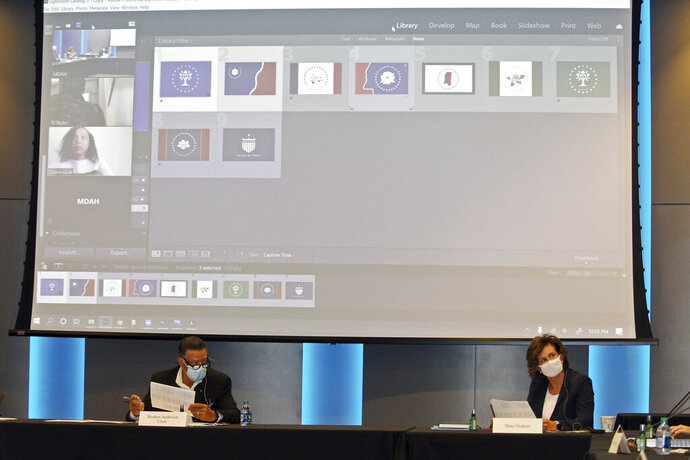 Reuben Anderson, seated left, and Mary Graham, and other members of a commission that will recommend a new Mississippi state flag, discuss flag choices, Friday, Aug. 14, 2020, at the Two Mississippi Museums in Jackson, Miss. The screen above Anderson and Graham shows people participating remotely in the commission meeting and images of nine flags chosen as finalists, although a graphic artist was set to make small changes to some of the designs. Mississippi recently retired the last state flag in the U.S. that included the Confederate battle emblem. (AP Photo/Emily Wagster Pettus)