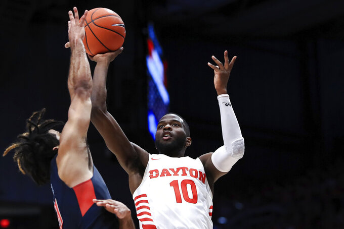 FILE - In this Feb. 22, 2020, file photo, Dayton's Jalen Crutcher drives to the basket against Duquesne's Sincere Carry, left, in the second half of an NCAA college basketball game in Dayton, Ohio. Dayton finished third in The Associated Press college basketball poll, Wednesday, March 18, 2020, behind breakout stars Jalen Crutcher and Obi Toppin. (AP Photo/Aaron Doster, File)