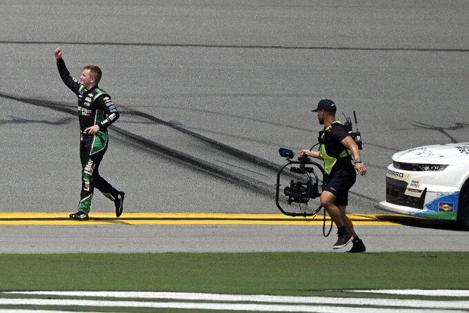 Justin Haley, left, waves to fans after winning a NASCAR Xfinity Series auto race as a TV camera man gives chase at Daytona International Speedway, Saturday, Aug. 28, 2021, in Daytona Beach, Fla. (AP Photo/Phelan M. Ebenhack)