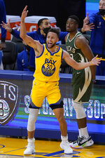 Golden State Warriors guard Stephen Curry (30) reacts after being fouled by Milwaukee Bucks forward Thanasis Antetokounmpo, rear, during the second half of an NBA basketball game in San Francisco, Tuesday, April 6, 2021. (AP Photo/Jeff Chiu)