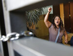 An anti-government protester shouts slogans after she and other protesters entered the building of the Lebanese Association of Banks and locked the main entrance during ongoing protests against the banks and government in Beirut, Lebanon, Friday, Nov. 1, 2019. Lebanon's private banks have reopened after a two-week closure because of anti-government protests. The reopening on Friday follows Prime Minister Saad Hariri's resignation this week, a key demand of the protesters. (AP Photo/Hussein Malla)