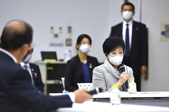 Tokyo Governor Yuriko Koike, right, delivers a speech during an opening plenary session of the three-party meeting on Tokyo 2020 Games additional costs due to the impact of the COVID-19 pandemic in Tokyo, Friday, Dec. 4, 2020. (Kazuhiro Nogi/Pool Photo via AP)