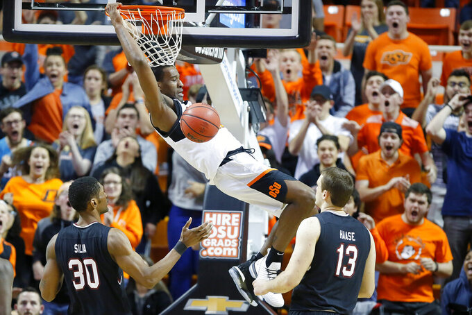 Oklahoma State's Cameron McGriff (12) dunks between South Carolina's Chris Silva (30) and Felipe Haase (13) during an NCAA college basketball game in Stillwater, Okla., Saturday, Jan. 26, 2019.(Bryan Terry/The Oklahoman via AP)