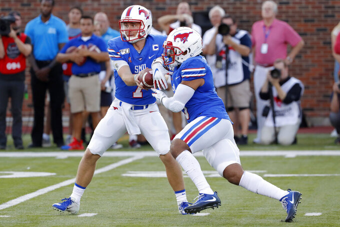 SMU quarterback Shane Buechele (7) hands the ball to running back Xavier Jones, right, during the first half of an NCAA college football game against Tulsa, Saturday, Oct. 5, 2019, in Dallas, Texas. (AP Photo/Roger Steinman)