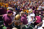 Minnesota mascot Goldy the Golden Gopher, front center, is helped up after fans collapsed the fence around the field and trapped the mascot after an NCAA college football game against Colorado, Saturday, Sept. 18, 2021, in Boulder, Colo. Minnesota won 30-0. (AP Photo/David Zalubowski)