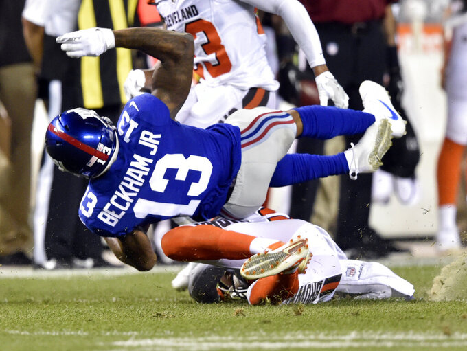 "FILE - In this Aug. 21, 2017, file photo, New York Giants wide receiver Odell Beckham (13) is tackled by Cleveland Browns strong safety Briean Boddy-Calhoun in the first half of an NFL preseason football game in Cleveland. Odell Beckham Jr. says former Browns defensive coordinator Gregg Williams instructed his players to ""take me out"" of a preseason game in 2017. The Pro Bowl wide receiver sustained an ankle injury when Cleveland's Briean Boddy-Calhoun cut his legs out while he was with the New York Giants. Beckham said current Cleveland players told him that Williams instructed them to ""take me out of the game, and it's preseason."" (AP Photo/David Richard, File)"
