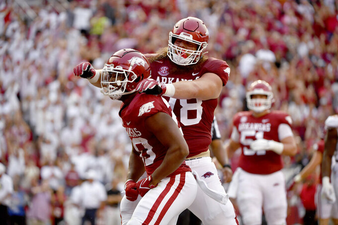 Arkansas running back Dominique Johnson (20) celebrates with Dalton Wagner (78) after scoring a touchdown against Texas during the first half of an NCAA college football game Saturday, Sept. 11, 2021, in Fayetteville, Ark. (AP Photo/Michael Woods)