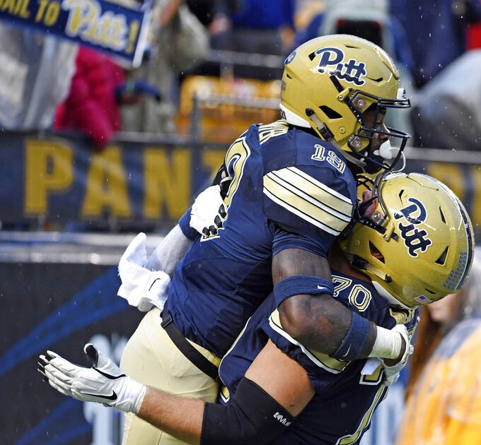FILE- In this Oct. 27, 2018, file photo, Pittsburgh's Stefano Millin picks up V'Lque Carter after Carter's touchdown against Duke in the third quarter of an NCAA college football game in Pittsburgh. Millin, a grad transfer from Kent State, has been the best player on an offensive line that has paved the way for one of the best running games in the country. (Chaz Palla/Pittsburgh Tribune-Review via AP, File)