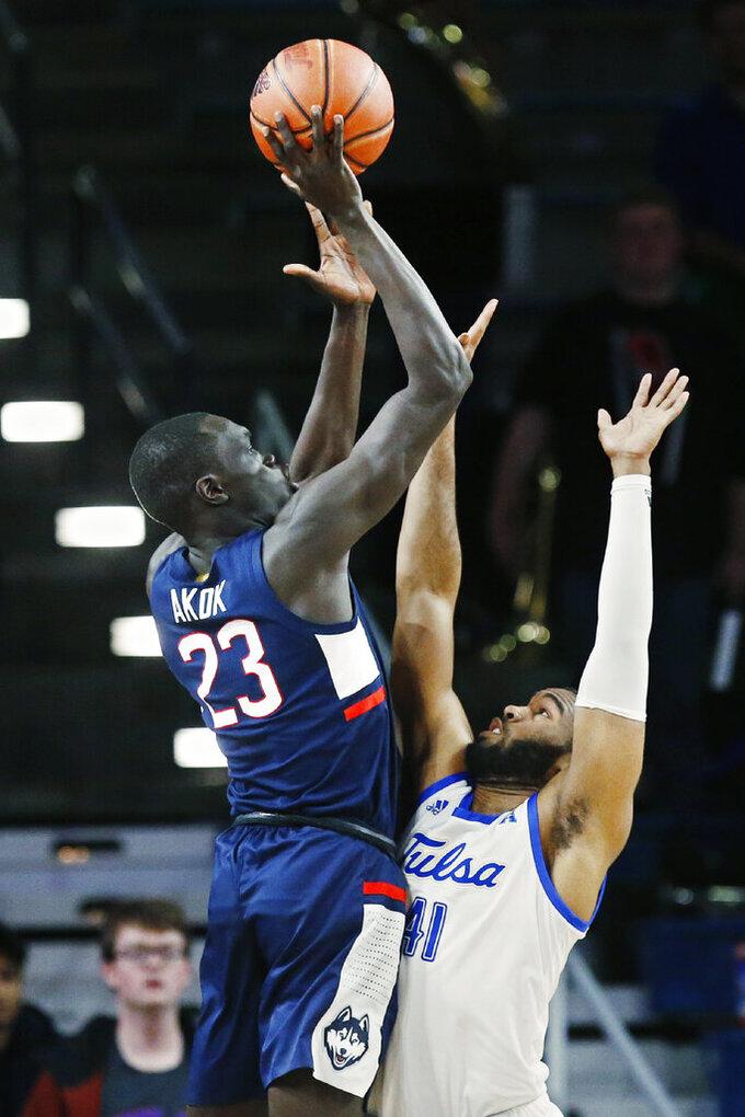 Connecticut forward Akok Akok (23) shoots over Tulsa forward Jeriah Horne (41) during the second half of an NCAA college basketball game in Tulsa, Okla., Thursday, Feb. 6, 2020. (AP Photo/Sue Ogrocki)