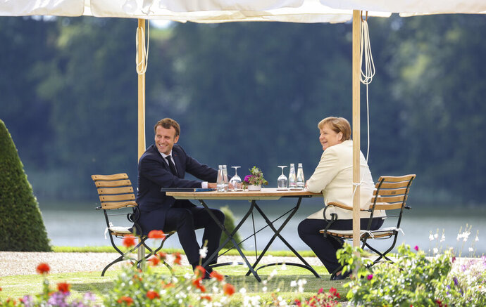 German Chancellor Angela Merkel and French President Emmanuel Macron, left, talk during a bilateral meeting at the German government's guest house Meseberg Castle in Gransee near Berlin, Germany, Monday, June 29 2020. The meeting takes place ahead of Germany's EU Council Presidency in the second half of 2020. (Hayoung Jeon, Pool via AP)