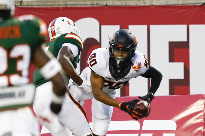 Oklahoma State wide receiver Brennan Presley (80) makes a reception for a touchdown in against Miami linebacker Keontra Smith during the first half of the Cheez-it Bowl NCAA college football game, Tuesday, Dec. 29, 2020, in Orlando, Fla. (AP Photo/John Raoux)