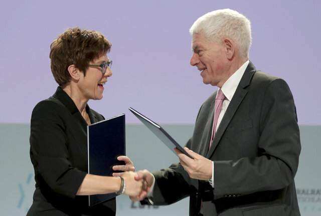 German Defence Minister Annegret Kramp-Karrenbauer, left, and Josef Schuster, President of the Central Council of Jews in Germany, right, shake hands after they signed a treaty on rabbis in the German forces in Berlin, Germany, Friday, Dec. 20, 2019. (AP Photo/Michael Sohn)