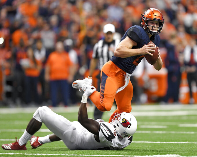 Syracuse quarterback Eric Dungey, top, tries to break the grasp of Louisville defensive end Tabarius Peterson during the first half of an NCAA college football game in Syracuse, N.Y., Friday, Nov. 9, 2018. (AP Photo/Adrian Kraus)