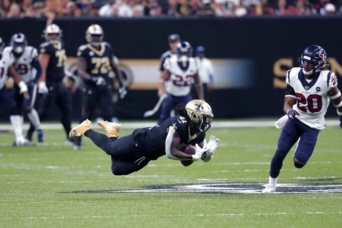 New Orleans Saints running back Alvin Kamara (41) falls to the turf as Houston Texans strong safety Justin Reid (20) pursues in the second half of an NFL football game in New Orleans, Monday, Sept. 9, 2019. (AP Photo/Bill Feig)
