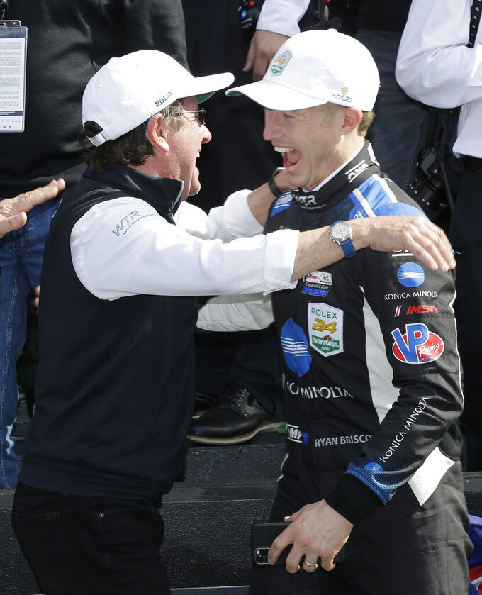 Konica Minolta Cadillac DPi-V.R driver Ryan Briscoe, right, and team owner Wayne Taylor, left, celebrate in Victory Lane after winning the Rolex 24-hour auto race at Daytona International Speedway, Sunday, Jan. 26, 2020, in Daytona Beach, Fla. (AP Photo/Terry Renna)