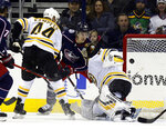 Columbus Blue Jackets forward Ryan Dzingel, center, scores between Boston Bruins defenseman Steven Kampfer, left, and goalie Tuukka Rask, of Finland, during the first period of an NHL hockey game in Columbus, Ohio, Tuesday, March 12, 2019. (AP Photo/Paul Vernon)