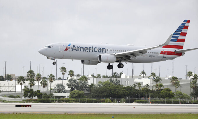 FILE - In this July 27, 2020, file photo, an American Airlines Boeing 737-823 lands at Miami International Airport in Miami. Flight attendants at American Airlines say they are sometimes forced to sleep in airports because the airline fails to book hotel rooms for employees on the road. Unions for flight attendants and pilots filed grievances against American this week, charging the airline with violating their contracts and putting employees in danger. The president of the flight attendants' union says some of her members have slept outside baggage claim because they didn't have a hotel room. Leaders of the pilots' union say pilots have been put in unsafe hotels or told to walk to the hotel in the middle of the night when flights arrive late. (AP Photo/Wilfredo Lee, File)