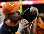 FILE - In this Jan. 7, 2019, file photo, Clemson head coach Dabo Swinney kisses the championship trophy after the NCAA college football playoff championship game against Alabama in Santa Clara, Calif. (AP Photo/David J. Phillip, File)